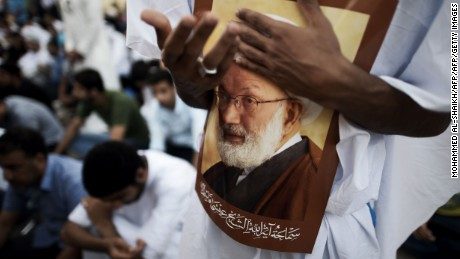 Supporters hold a portrait of Bahraini Shiite cleric Sheikh Isa Qassim at a protest.