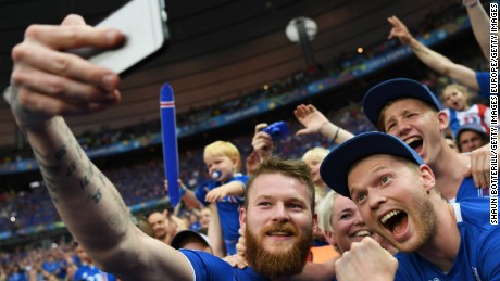 Aron Gunnarsson of Iceland takes a selfie photographs with Iceland fans.
