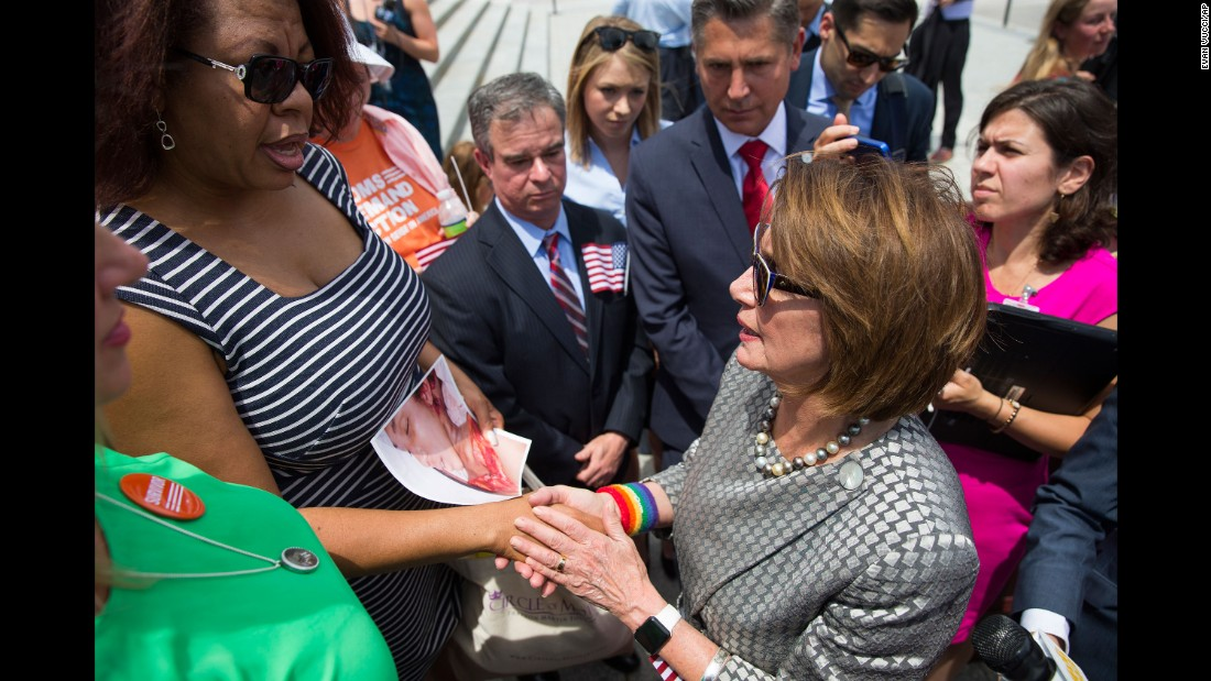 Washington resident Nardyne Jefferies, holding a photo of her daughter, Brishell, 16, who died in gun violence, meets with House Minority Leader Nancy Pelosi after a June 22 news conference on gun legislation on Capitol Hill.