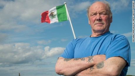 Michael Forbes poses for a photograph beside the Mexican flag he erected alongside Donald Trump's International Golf Links course, north of Aberdeen on the East coast of Scotland, on June 21.