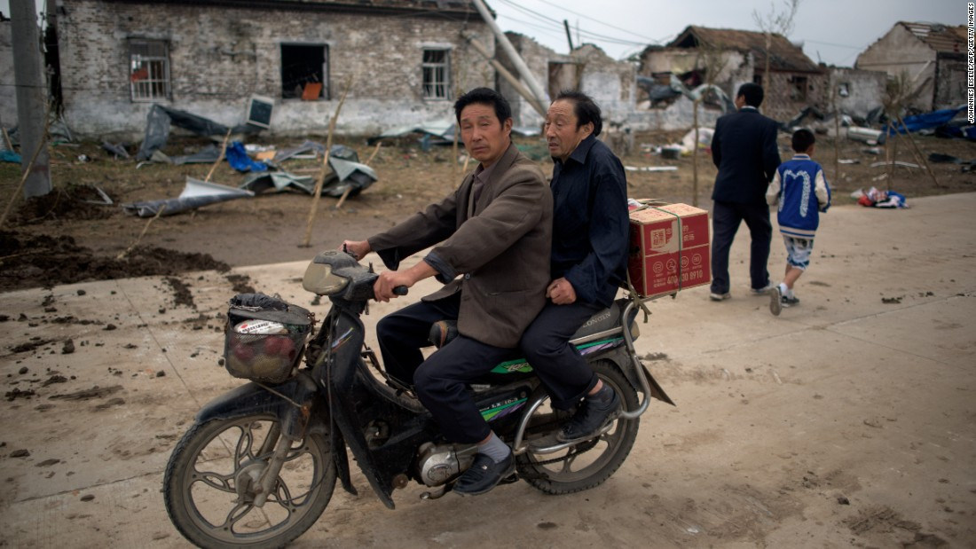 Residents on a motorbike pass through the heavily damaged village of Funing on June 24.