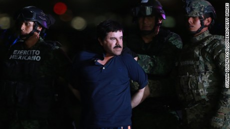 Joaquin Guzman, the world's most wanted-drug trafficker, is escorted by Mexican security forces at a Navy hangar in Mexico City, Mexico, on Friday, Jan. 8, 2016. Guzman, known as El Chapo, was recaptured by Mexican authorities six months after he escaped from a maximum-security prison, slipping into an elaborate tunnel under his shower and humiliating the government.