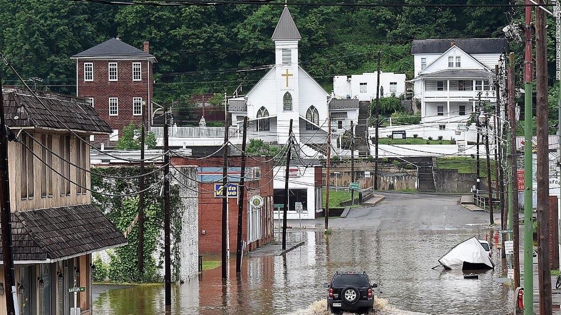 An SUV makes a wake along a flooded street in Richwood, West Virginia, on Friday, June 24.