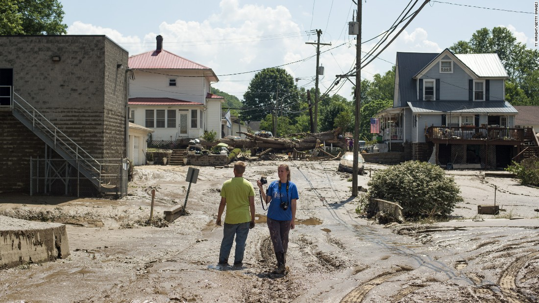 People survey a mud-covered street after the floodwaters of the Elk River receded in Clendenin on Saturday, June 25.