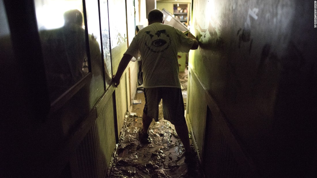Larry Brooks walks down the muddy hallway of his trailer in Elkview, West Virginia, on June 25. Brooks said he lost about 95% of the personal belongings in his home.