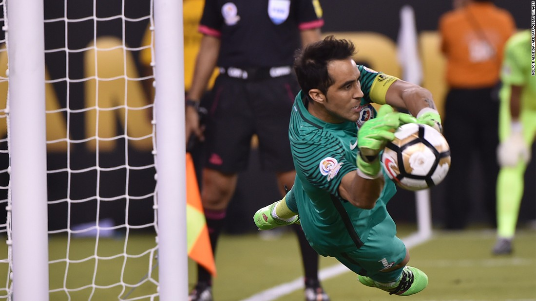 Chile's goalie Claudio Bravo stops a shot by Argentina's Lucas Biglia (out of frame).