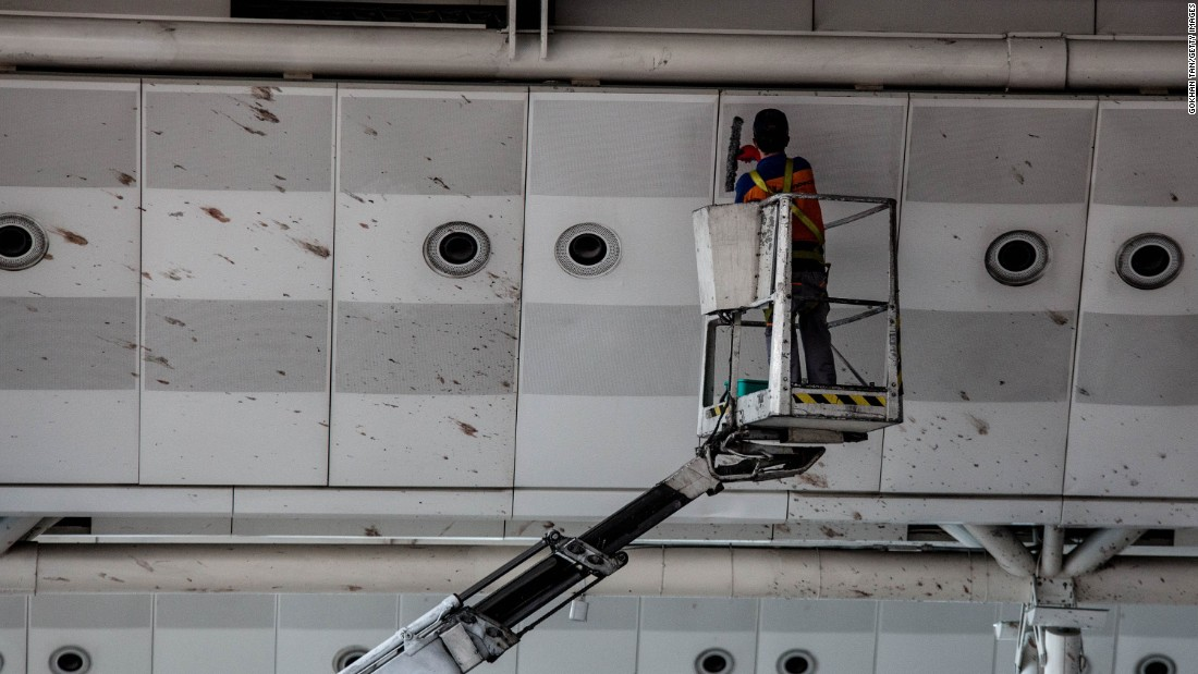 A worker cleans blood from the upper walls of the international departure terminal.