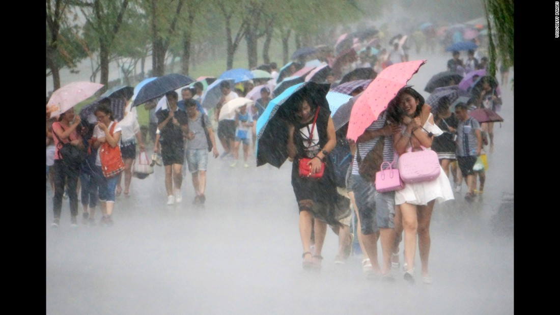 "People use umbrellas as they walk in strong winds and heavy rain near West Lake as Typhoon ""Soudelor"" approaches on August 7, 2015 in Hangzhou, Zhejiang Province of China."