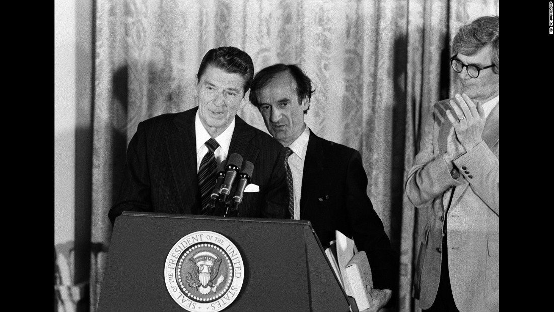 "Then-President Ronald Reagan and Elie Wiesel (behind Reagan), chairman of the United States Holocaust Memorial Council, take part in a ""day of remembrance"" ceremony in the East Room of the White House on April 30, 1981."