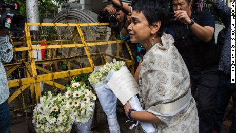 A woman leaves flowers at a roadblock near the cafe. Bangladesh was observing two days of national mourning.