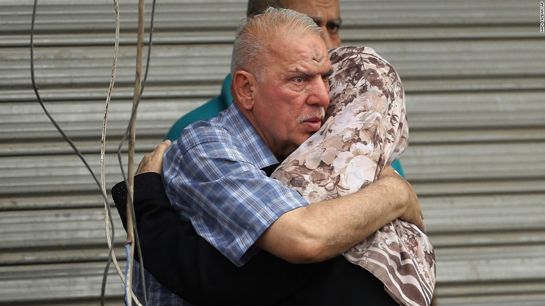 People hug near the site of the Karrada blast.