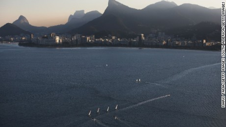 Sailboats sail in the polluted Guanabara Bay, venue site of the Olympic sailing events.