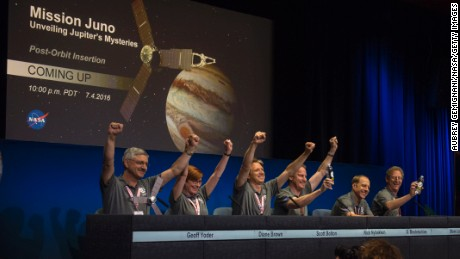 Members of the Juno team celebrate at a press conference after they received confirmation from the Juno spacecraft that it had completed the engine burn and successfully entered into orbit around Jupiter.