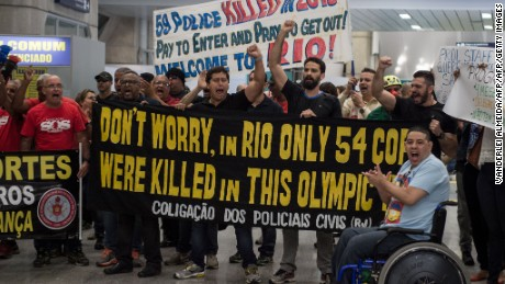 "Police officers and firemen demonstrate at the international arrivals gate as they protest against the government for delay in their salary payments at Tom Jobim International Airport in Rio de Janeiro, Brazil, July 4, 2016. The Police has been mounting street protests since last week, saying that they have not been fully paid for months as Rio state's budget hovers on the edge of bankruptcy. Earlier this month, the state authorities in Rio declared ""state of public calamity ""about a major crisis budget in order to release emergency funds to finance the Olympic Games due to start in August. / AFP / VANDERLEI ALMEIDA        (Photo credit should read VANDERLEI ALMEIDA/AFP/Getty Images)"