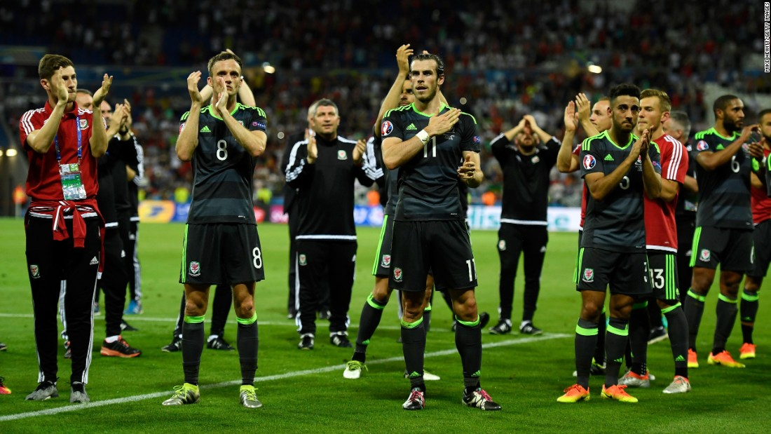 Welsh players applaud their fans after the loss in Lyon, France.