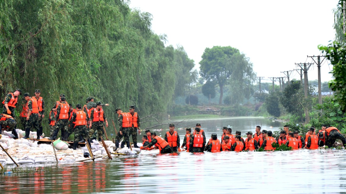 Chinese soldiers carry sandbags to reinforce a lake dyke in Wuhan on July 5.