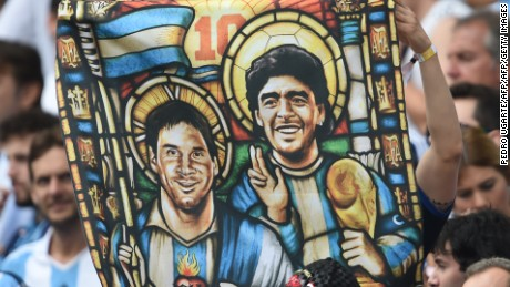 Lionel Messi and Diego Maradona depicted as saints on a supporter's flag. Maradona holds the World Cup trophy while Messi, crucially, does not.