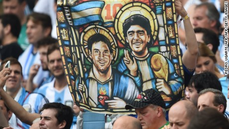 An Argentina's fan holds an image of Argentina's forward Lionel Messi and former footballer Diego Maradona as Saints, before for the Group F football match between Nigeria and Argentina at the Beira-Rio Stadium in Porto Alegre during the 2014 FIFA World Cup on June 25, 2014.   AFP PHOTO / PEDRO UGARTE        (Photo credit should read PEDRO UGARTE/AFP/Getty Images)