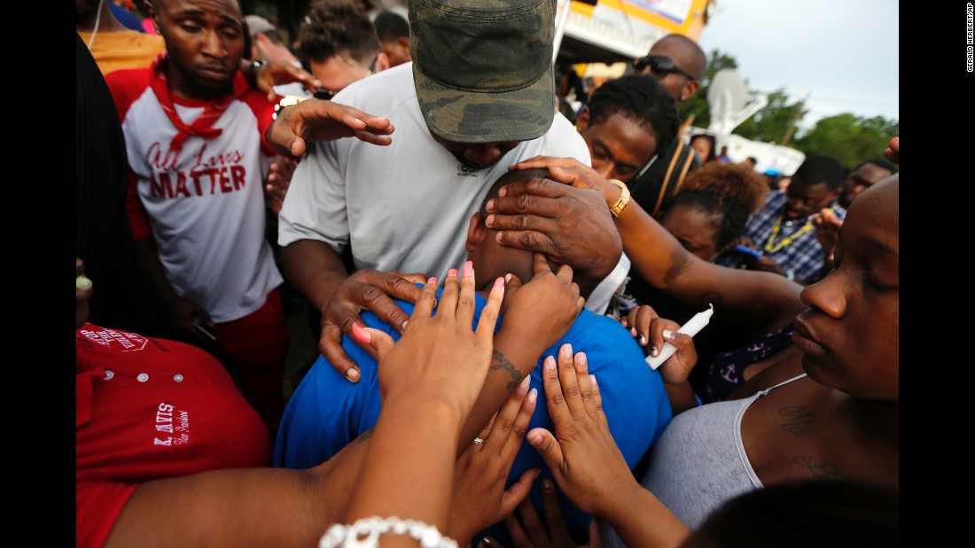 Hands of comfort extend to Cameron Sterling, the son of Alton Sterling, outside the convenience store where Alton Sterling was shot and killed by police.