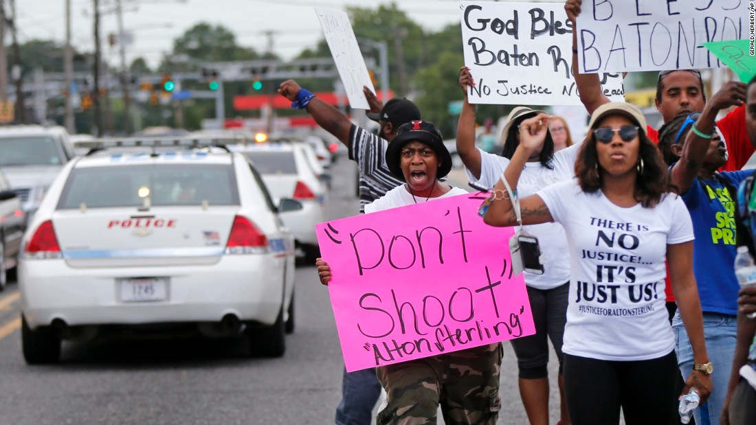 People in Baton Rouge demonstrate July 6 as police cars pass the convenience store where Alton Sterling was shot.