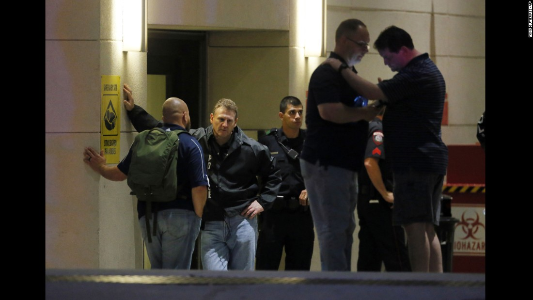 Law enforcement officials wait outside the emergency room entrance of the Baylor University Medical Center.