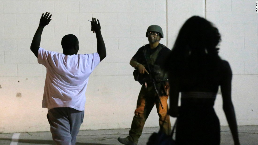A man raises his hands as he walks near a law enforcement officer in Dallas.