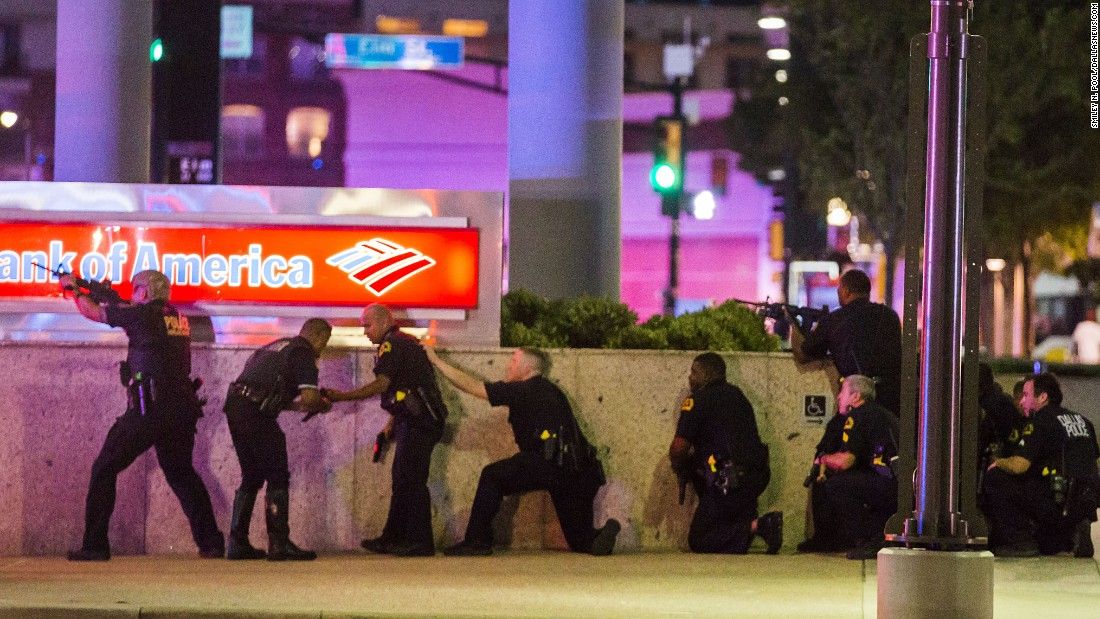 "Dallas Police take position after shots are fired. Pool said the police were ""very focused, very on their game."" This image, showing a line of officers against the wall with their guns drawn, was made as Pool looked down the street while he was squeezed between some cars and behind a police officer for cover."