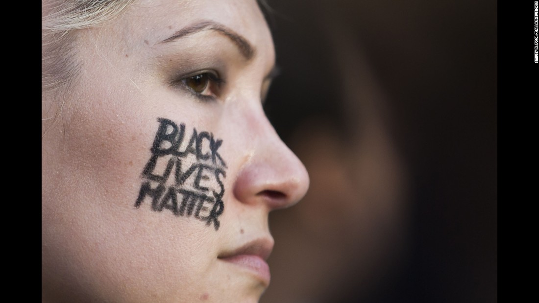 "A woman with ""Black Lives Matter"" on her cheek joins other protesters. As the march began and although the police presence was considerable, Pool said everyone was positive."