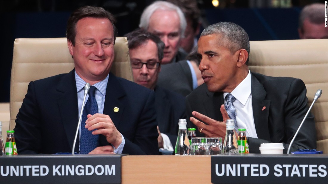 British Prime Minister David Cameron, left, and Obama chat during a North Atlantic Council meeting at the summit in Warsaw on July 9.