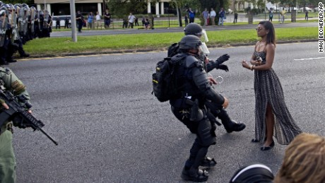 A protester is grabbed by police officers in riot gear after she refused to leave the motor way in front of the the Baton Rouge Police Department Headquarters in Baton Rouge, La., Saturday, July 9, 2016. Several hundred protesters, including members of the New Black Panther party, blocked the roadway causing police to close the road and move the crowd with riot police. Several protesters were arrested.(AP Photo/Max Becherer)