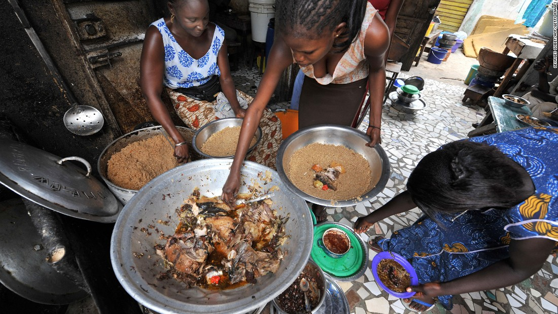 """As income goes up, we can consume and buy more good things, healthier things like fruits, vegetables, fresh fish, stuff like that. But we can and do also buy unhealthy things -- processed meats, sugary drinks, highly processed food,"" Haddad says.  <br /><br />Pictured here, women prepare a traditional Senegalese dish of rice and fish at a street restaurant in Dakar."