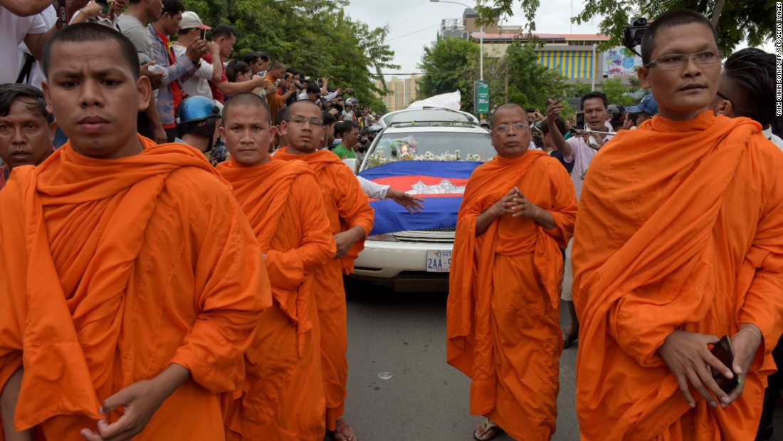 Buddhist monks walk in front of the car transporting Kem Ley''s body.