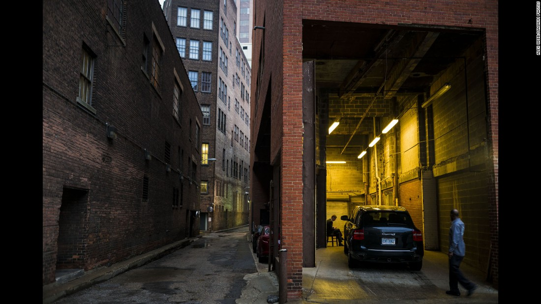 "A car is parked in a garage in a downtown alley. Webb said this is his favorite photograph from his time in the city. ""It's nearing dusk in the photo. There are a number of them like that I like, just before dark or just after dawn, where you are looking in,"" he said. ""It has a noirish quality -- like a detective film that is shot just at dusk. It was just a moment."""