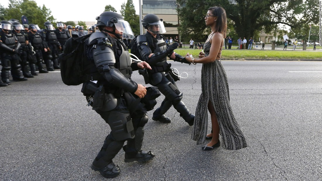 A young woman stands frozen -- clad in a flowing dress, armed only with a cell phone -- in the middle of a street as a pair of police officers move to arrest her. She was one of hundreds of protesters who blocked a Baton Rouge roadway during anti-police brutality demonstrations. The symbolism of a single person's nonviolent resistance against a large, heavily armed opposition is being viewed by some as the photo that symbolizes the week's protests.
