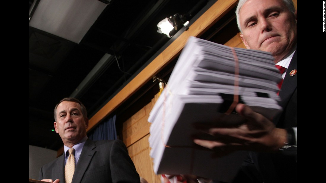 Former Speaker of the House John Boehner hands a copy of the stimulus bill to Pence after the House of Representatives voted to pass it on February 13, 2009. The bill passed the House along a strict party vote of 246-183.