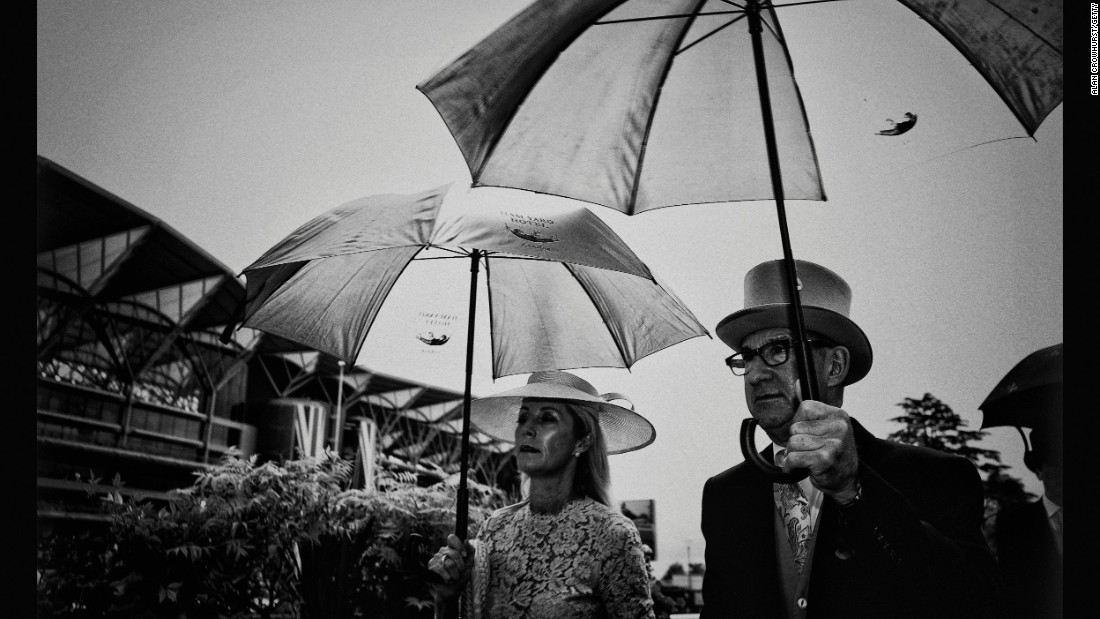 Though racegoers are dressed to the nines, in Britain there are no guarantees it won't rain. Pictured, racegoers coupling sartorial elegance with England's obligatory umbrellas.