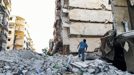 Dr. Samer Attar walking across the rubble of bombed out buildings in rebel-held eastern Aleppo.