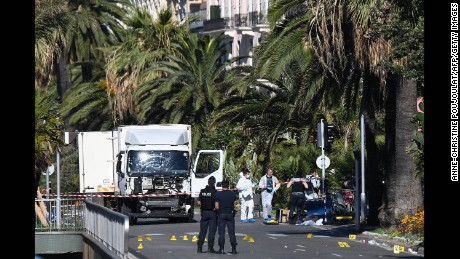 Forensics officers and policemen look for evidences near a truck on the Promenade des Anglais seafront in the French Riviera town of Nice on July 15, 2016, after it drove into a crowd watching a fireworks display.
