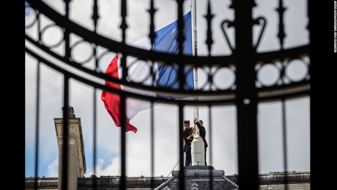 French Republican guards place the French flag at half-staff at the Elysee Palace in Paris on July 15.