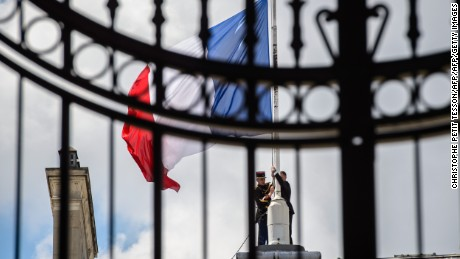 French Republican guards place the French flag half-staff at the Elysee presidential Palace on Friday.