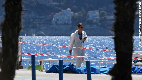 A forensic expert examines dead bodies covered with a blue sheet on the Promenade des Anglais seafront in the French Riviera city of Nice.