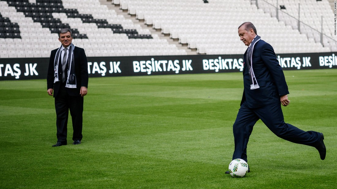 Erdogan, right, kicks a soccer ball while Former Turkish President Abdullah Gul watches at Besiktas soccer club's new Vodafone Arena on its opening day in Istanbul on Sunday, April 10.