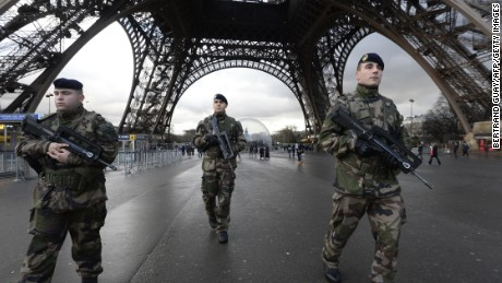 French soldiers patrol in front of the Eiffel Tower on January 8, 2015 in Paris as the capital was placed under the highest alert status a day after heavily armed gunmen shouting Islamist slogans stormed French satirical newspaper Charlie Hebdo and shot dead at least 12 people in the deadliest attack in France in four decades. A  huge manhunt for two brothers suspected of massacring 12 people in an Islamist attack at a satirical French weekly zeroed in on a northern town Thursday after the discovery of one of the getaway cars. As thousands of police tightened their net, the country marked a rare national day of mourning for Wednesday's bloodbath at Charlie Hebdo magazine in Paris, the worst terrorist attack in France for half a century. AFP PHOTO / BERTRAND GUAY        (Photo credit should read BERTRAND GUAY/AFP/Getty Images)