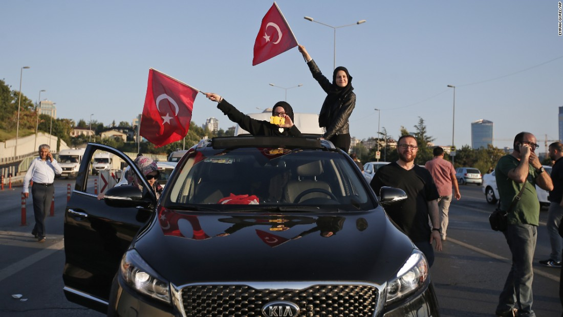 Turkish people wave national flags from a car in Istanbul.