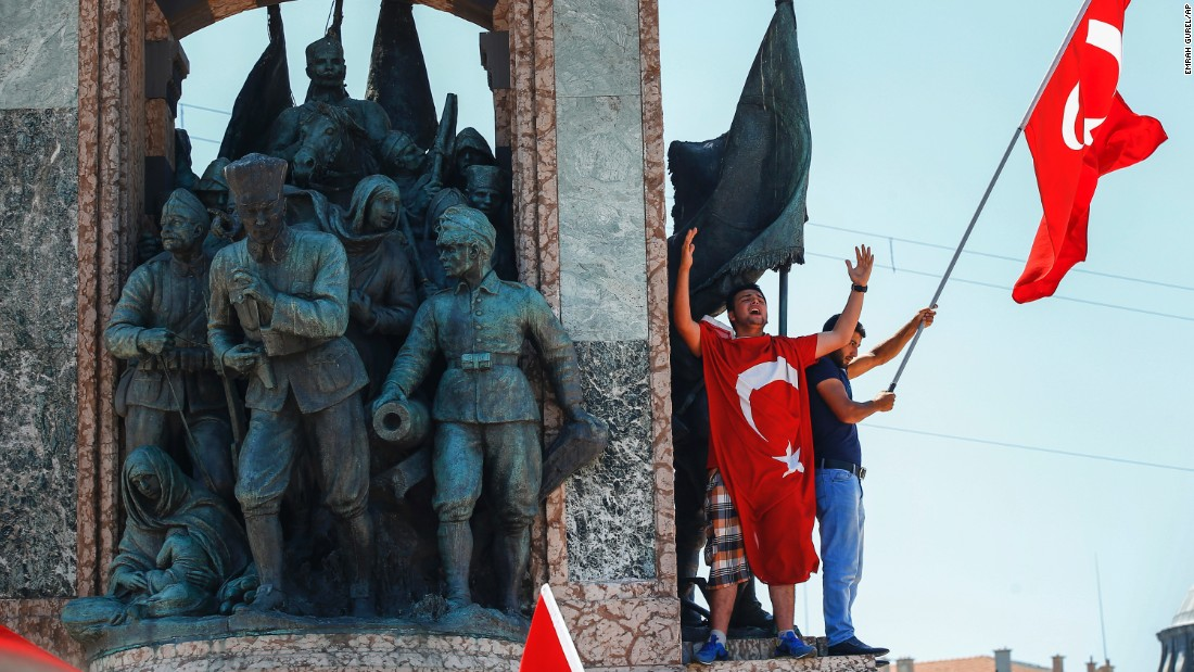 People protesting against the coup wave a Turkish flag on top of a monument in Istanbul's Taksim Square.