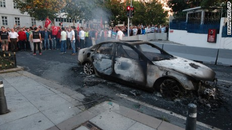 Turkish people look at a burned car in Istanbul on Saturday.