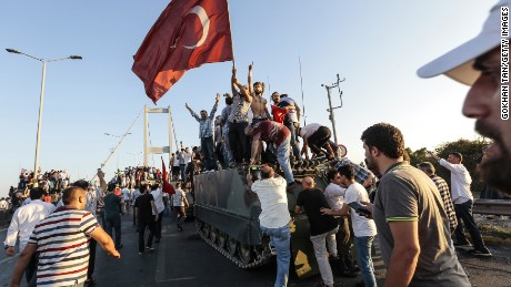 Supporters of Turkish President Recep Tayyip Erdogan wave flags as they capture a Turkish Army APC.