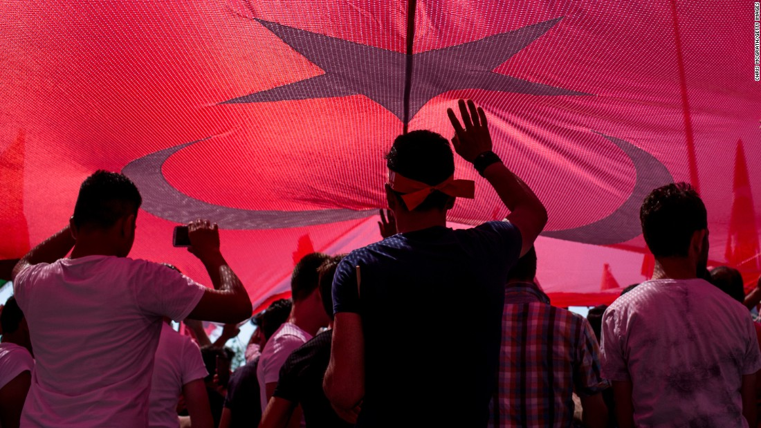 People stand under a huge Turkish flag during a march around Kizilay Square in Ankara in reaction to the attempted coup.