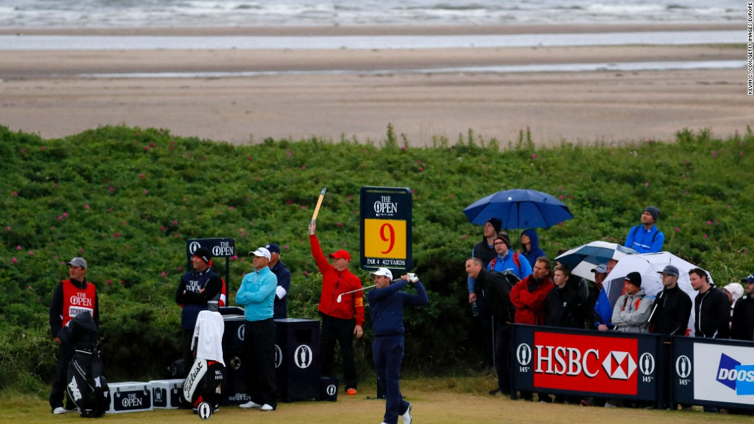 The umbrellas are up and the sea breeze is picking up as Charl Schwartzel of South Africa hits his tee shot on the ninth hole at Royal Troon.