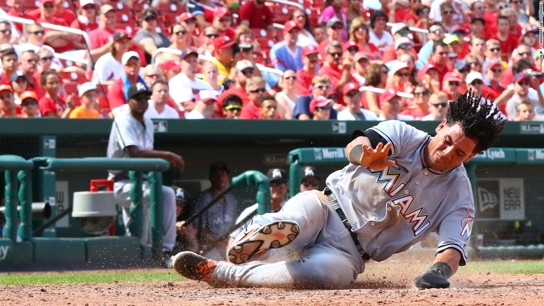 Miami's Yefri Perez slides into home, scoring a run at St. Louis on Sunday, July 17.
